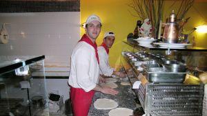 Roomalaisia valkopaitaisia ja punahuivisia pizzakokkeja työssä ravintolan keittiössä.