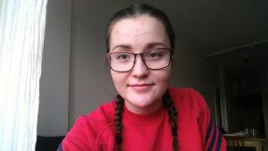 Karolina Junell: Tittar in i kameran. Har glasögon och flätor, och en röd tröja.