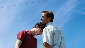 Elio (Timothée Chalamet) nojaa päätään Oliverin (Armie Hammer) rintaa vasten. Sininen taivas taustalla.