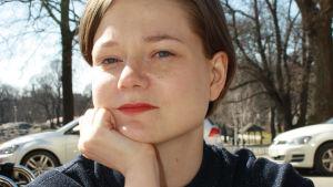 Bild av Johanna Frid som ser in i kameran med hand under hakan