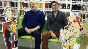 Asterix-sarjakuvien käsikirjoittaja Jean-Yves Ferri ja kuvittaja Didier Conrad istuvat pahvisten sarjakuvahahmojen välissä