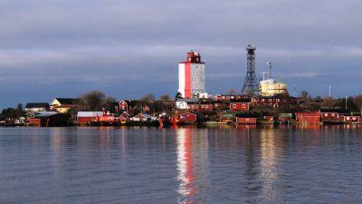 Utsikt från havet över Utö, där den rödvita fyren speglas i vattnet.