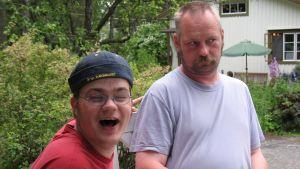 två män sitter i en trädgård på sommaren