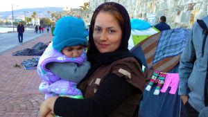 flyktingkvinna med ett barn i famnen