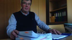 Peter Siggberg bläddrar i mappen med alla dokument över utredningarna i Merituulen koulu.