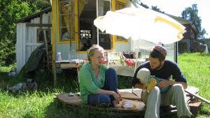Vilma och Per-Viktor utanför sitt mobila hus, ett blått trähus med hjul under. På bilden finns också familjens förstfödda baby.
