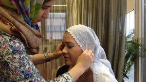 Sonila Naziri visar hur man knyter en hijab. Modellen är Anne-Lie Nyman.