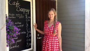Nora Garusi står vid en skylt där det står Café Dagny.