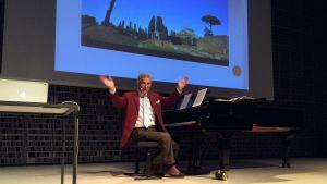Mestro Adriano Bassi vertailee Sibeliuksen ja italialaisten aikalaisten musiikkia Helsingin Musiikkitalossa 2015. Taustalla kuva pinjoista Rooman katakombeilla, joista Ottorino Respighi sävelsi hyvin sibeliusmaisen teoksen.