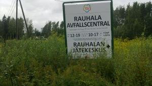 Skylt i högt gräs som berättar vilka tider Rauhala avfallscentral i Pargas har öppet.