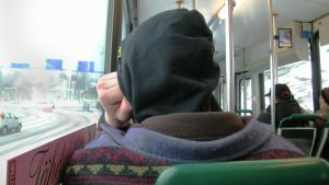 En person sitter i en buss, ryggen vänd mot kameran.
