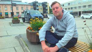 Kristian Karnell sitter på en bänk på Rådhustorget i Ekenäs.