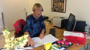 En kvinna i blåbrokig blus sitter och bläddrar i en tidsbokningskalender, på bordet finns dator, skrivare, papper, dekorationer.