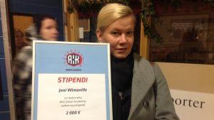 Informationschef Anu Haapalainen från bilsportsförbundet AKK med ett stipendium på 2 000 euro till Joni Wiman.