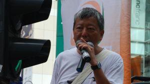 Lee Cheuk-yan står med mikrofon i hand framför en skara människor.  trationer sedan han blev politiskt aktiv som studerande.