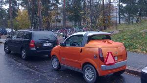 orange mopedbil so mstår parkerad bakom en personbil