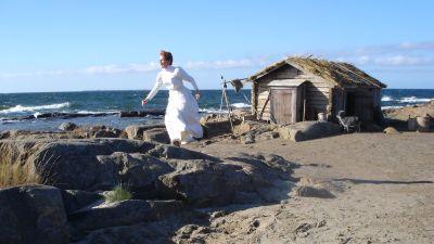 Karakrären Hanna springer i vita kläder på klippor ute i skärgården.