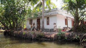 Intialainen perhe vilkittaa kotitalonsa edustalla Keralassa.