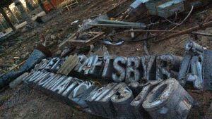 """En gammal trasig skylt med texten """"Arbetskraftsbyrå Työvoimatoimisto"""" ligger på marken, i bakgrunden är industrihall som håller på att rivas."""