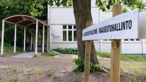 """En vit träbyggnad, skylten """"Landsbygdsförvaltning Maaseutuhallinto"""" till höger, svart text på vit botten. Ett grönt lövträd."""