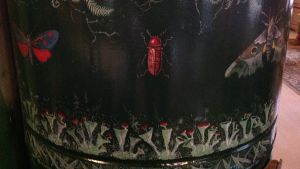 En spis av plåt med målade insekter på.