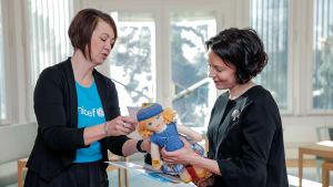 Presidentfrun Jenni Haukio tar emot en  Unicefdocka av Yvonne Korenius, ordförande för den frivilliga UNICEF-gruppen i Raseborg.