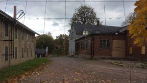 Byggnader i Billnäs bruk sedda genom ett stängselnät. Höstlöv.