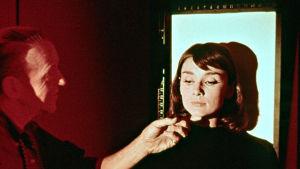 Fred Astaire tutkii Audrey Hepburnin kasvoja. Kuva elokuvasta Rakastunut Pariisissa.
