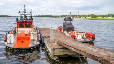 Två sjöräddningsbåtar ligger förtöjda vid en brygga.