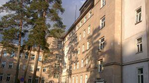 Baksidan av huvudbyggnaden vid Mjölbolsta sjukhus. En stor äldre stenbyggnad i 4-5 våningar.