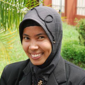 En muslimsk kvinna i Malaysia tittar leende in i kameran.