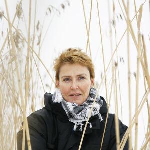 Författaren Minna Lindeberg iklädd en svart jacka och svartvit sjal står ibland vass och tittar in i kameran.