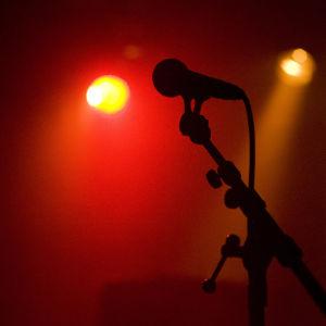 En mikrofon står i ett stativ på en scen där röda scenlampor lyser.