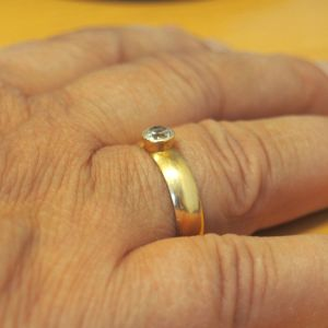 Käsi, jossa timanttisormus sormessa.