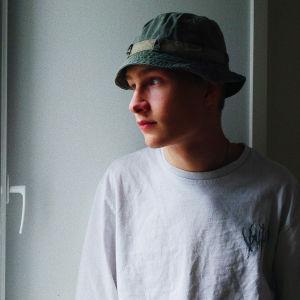 Nuori mies vihreässä kalastajalakissa katsoo vasemmalle melko ilmeettömänä. Päällä on valkoinen paita ja hän seisoo vaalean seinän edessä.