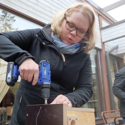 Kymin seurakunnan kirkkoherra Anna-Tiina Järvinen poraa ruuvia linnunpönttöön