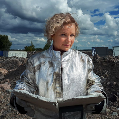 Minna Joenniemi avaruuspuvussa lukemassa tulevaisuuden kirjaa