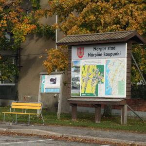 En infoskylt med kartor över Närpes. Till vänster om skylten två gula parkbänkar.