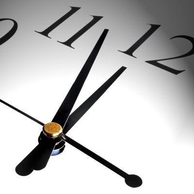 Närbild av analog klocka som är tre minuter i tolv.