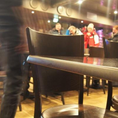 tarjoilija ohittaa pöydän