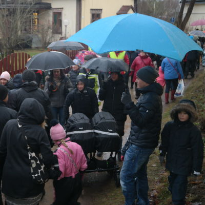 Folk i regnet i en smal gränd på Pargas julmarknad