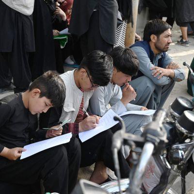 Afghaner fyller i dokument för att kunna lämna landet. utanför den brittiska och kanadensiska ambassaden i Kabul 19.8.2021