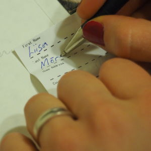 Nainen kirjoittaa nimeään paperiin, häiden kiitoskortti taustalla.