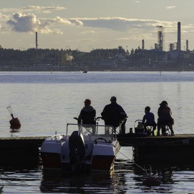 Perhe istuu laiturilla kalastamassa Porvoon öljyjalostamon siintäen taivaanrannassa.