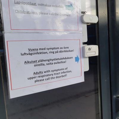 Skylt vid en av centralsjukhusets entrédörrar informerar besökare om coronaregler.