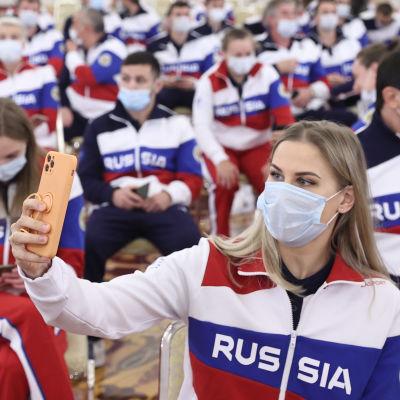 Ryska OS-sportare i munskydd tar en selfie tillsammans.
