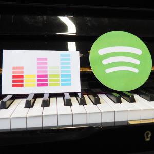 Deezerin, Spotifyn ja Groove Musicin logot pianon koskettimilla.