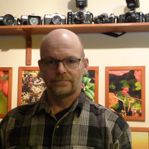 Tony Axberg  står framför några av sina naturfoton. Bakom skymtar också en del av hans omfattande kamerasamling