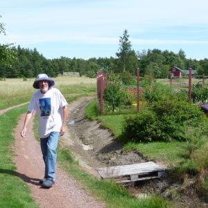 Janne Gröning promenerar på en sandväg. Bakom en del av hans trädgård i Keistiö i Iniö