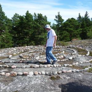 Janne Gröning går i en spiral av sten. Spiralen finns på ett berg i Keistiö, Åboland